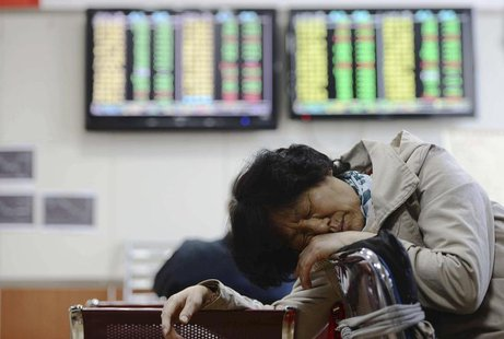 An investor naps in front of screens showing stock information at a brokerage house in Qingdao, Shandong province April 12, 2013. REUTERS/Ch