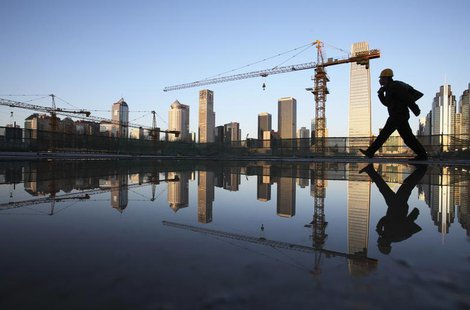 A worker walks past a pool of water inside a construction site in central Beijing, April 6, 2013. REUTERS/China Daily