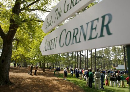 A sign points the way to the famed Amen Corner as patrons watch a practice round for the 2009 Masters golf tournament at the Augusta Nationa