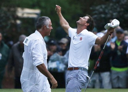 Adam Scott of Australia (R) celebrates with caddie Steve Williams after winning the 2013 Masters golf tournament on the second playoff hole