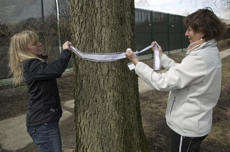 Carla Sloan (R) and Liz Ziehl, friends and neighbors of diplomat Anne Smedinghoff, 25, tie a ribbon on a tree in River Forest, Illinois, Apr