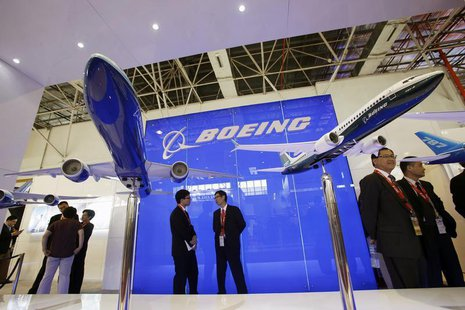 Visitors chat in front of models of the 777-300ER (L) and 737-8 MAX passenger planes, with a scale of 1:40, at the Boeing booth on the first
