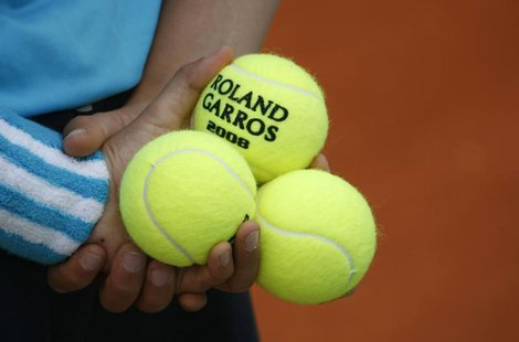 A ball boy holds tennis balls during an exhibition match ahead of the French Open tennis tournament at the Roland Garros stadium in Paris Ma