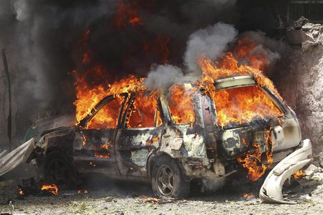 A car goes up in flames near the scene of a blast in Mogadishu April 14, 2013. REUTERS/Feisal Omar (SOMALIA - Tags: CIVIL UNREST POLITICS)