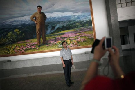 A Chinese visitor poses for a picture next to a portrait of then North Korean leader Kim Jong-il at an auditorium in Rason city, northeast o