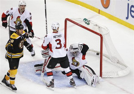 Ottawa Senators' Andrew Benoit (L) looks on as Boston Bruins' Nathan Horton celebrates his goal while Senators' Marc Methot (2nd R) watches