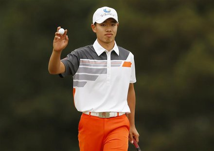 Amateur Guan Tianlang of China holds up his ball after sinking a par putt on the 18th green during final round play in the 2013 Masters golf