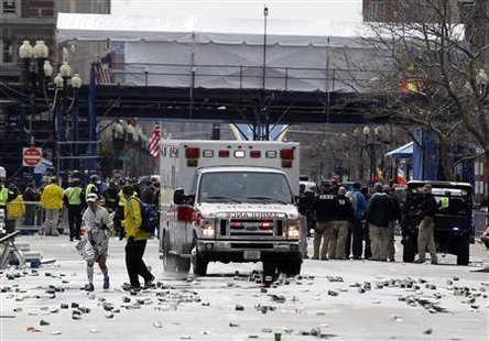 A runner is escorted from the scene after explosions went off at the 117th Boston Marathon in Boston, Massachusetts April 15, 2013.  (Reuters)