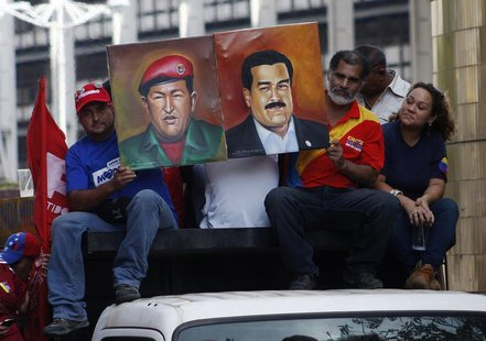 Supporters of Venezuela's President-elect Nicolas Maduro hold his portrait with one of Hugo Chavez during a demonstration in his favor, in C
