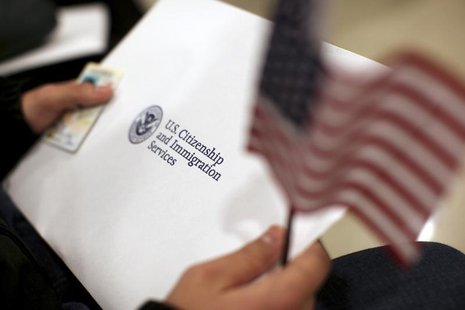 A man holds a U.S. flag while receiving his proof of U.S. citizenship during a ceremony in San Francisco, California January 30, 2013. REUTE