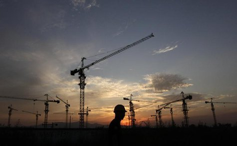 A worker walks past a residential construction site as the sun sets behind construction cranes on the outskirts of Beijing August 18, 2011.