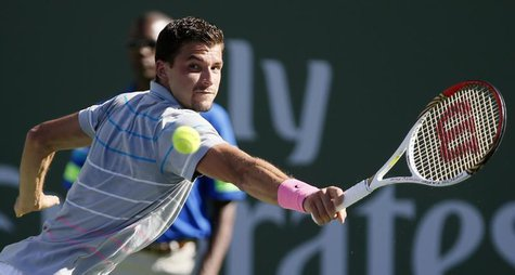 Grigor Dimitrov of Bulgaria returns a shot against Novak Djokovic of Serbia during their men's singles match at the BNP Paribas Open ATP ten