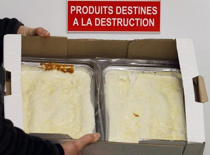 An employee displays a case of frozen beef lasagne dinners, removed from stores and prepared for destruction, under a sign on a door which r
