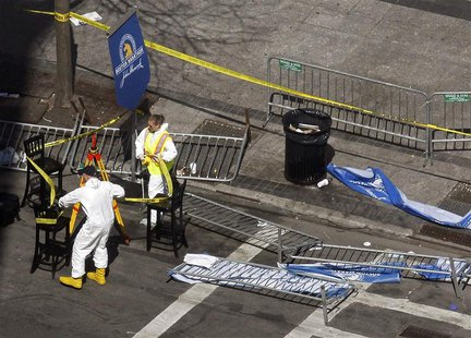Officials wrap crime scene tape around an area on Boylston Street a day after two explosions at the Boston Marathon in Boston, Massachusetts