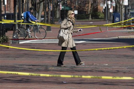 A commuter walks between police tapes a day after explosions hit the Boston Marathon in Boston, Massachusetts on April 16, 2013. REUTERS/Adr