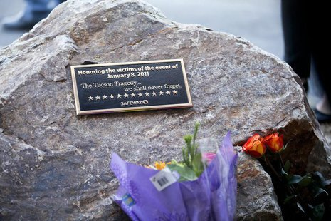 A plaque and flowers for victims of the January 8, 2011 Tucson shooting, are seen during a news conference at the Safeway grocery store park