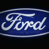 Ford cars are reflected in the company's logo at the carmakers' booth on media day at the Paris Mondial de l'Automobile, September 28, 2012.