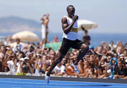 "Jamaican Olympic gold medallist Usain Bolt leaps ahead to win the ""Mano a Mano Men's 150 metres"" challenge on Copacabana beach in Rio de Jan"