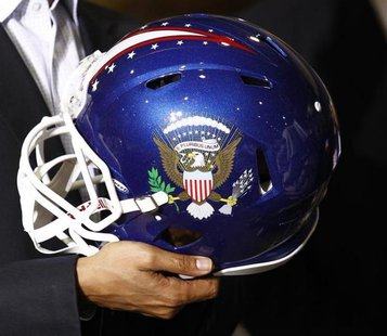 U.S. President Barack Obama holds a football helmet with the Presidential seal given to him during his visit to Riddell manufacturing facili