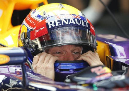 Red Bull Formula One driver Mark Webber of Australia puts on his helmet during the first practice session of the Chinese F1 Grand Prix at th