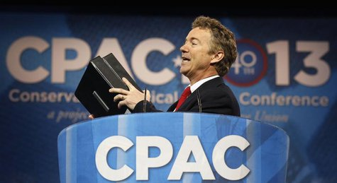 Senator Rand Paul of Kentucky holds up binders, a reference to his recent 13-hour filibuster, as he speaks at the Conservative Political Act