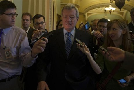 Sen. Max Baucus, (D-MT) is questioned by media at the U.S. Capitol in Washington December 31, 2012. U.S. REUTERS/Mary F. Calvert