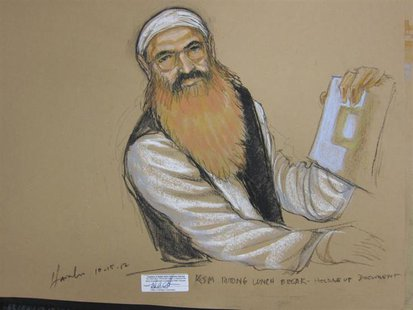 Khalid Sheikh Mohammed holds up a piece of paper in this artist's sketch during a court recess at pre-trail hearing at the U.S. Naval Base G