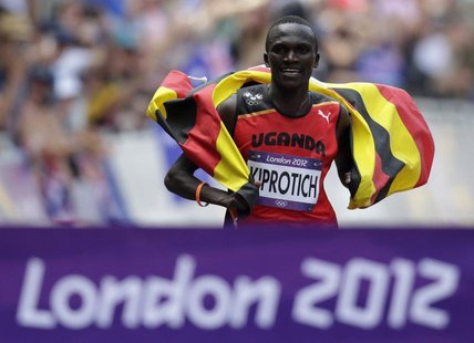 Uganda's Stephen Kiprotich celebrates with his national flag as he approaches the finish line to win the men's marathon in the London 2012 O