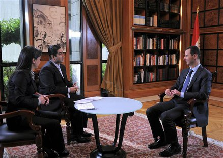 Syria's President Bashar al-Assad (R) attends an interview with Syrian television channel al-Ikhbariya in Damascus, in this handout photogra
