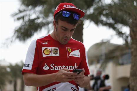 Ferrari Formula One driver Fernando Alonso of Spain checks his mobile phone in the paddock at the Bahrain International Circuit April 18, 20