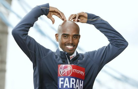 "Britain's double Olympic champion Mo Farah makes his trademark ""Mobot"" pose for photographers during a media event for the London Marathon,"