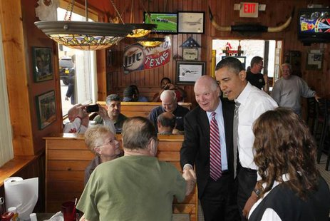 U.S. President Barack Obama stands next to U.S. Sen. Ben Cardin (D-Md) while greeting customers at the Texas Ribs & BBQ restaurant in Clinto