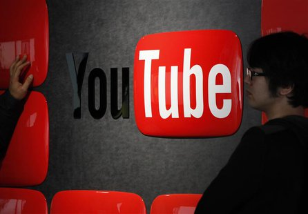 Visitors stand in front of a logo of YouTube at the YouTube Space Tokyo, operated by Google, in Tokyo February 14, 2013. REUTERS/Shohei Miya