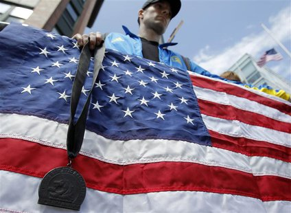 A Boston Marathon runner stands with his medal, which he dyed black, outside the Cathedral of the Holy Cross where United States President B