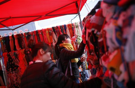 Customers selects hats at a street stall at the business area of Jiaozuo, China's central Henan province, December 20, 2012. REUTERS/Aly Son