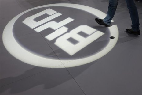 A man walks past a light flashing on the floor in the shape of the logo of BYD Auto during the media preview of the 10th China International