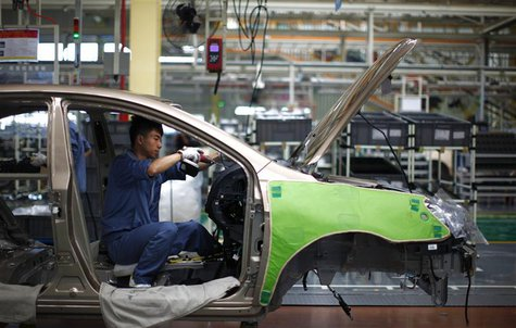 An employee works on the interior of a car along a Geely Automobile Corporation assembly line in Cixi, Zhejiang province in this June 21, 20
