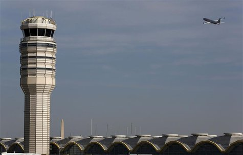 A jet departs Washington's Reagan National Airport next to the control tower outside Washington, in this February 25, 2013 file photo. REUTE
