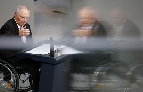 German Finance Minister Wolfgang Schaeuble is reflected in a window as he addresses the lower house of parliament Bundestag in Berlin, April
