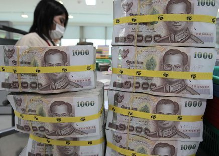 A bank employee counts Thai baht notes at Kasikornbank in Bangkok October 12, 2010. REUTERS/Sukree Sukplang