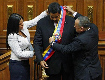 Venezuela's President Nicolas Maduro (C) receives the presidential sash from president of the National Assembly Diosdado Cabello (R), and Ma