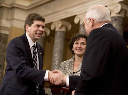 U.S. Sen. Mark Begich (L) (D-AK), accompanied by his wife Deborah Bonito, shakes hands with U.S. Vice President Dick Cheney at the Old Senat