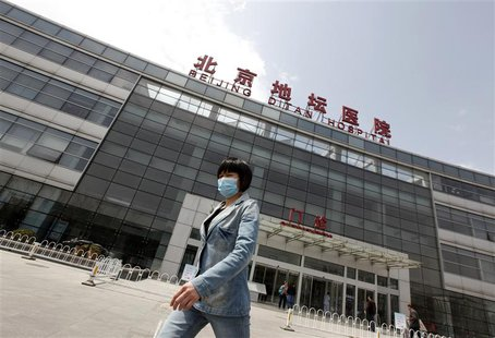 A woman wearing a mask walks outside the Ditan Hospital, where a child with a new strain of bird flu is undergoing treatment, in Beijing Apr