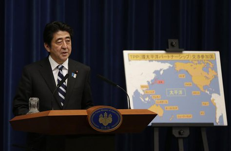 Japan's Prime Minister Shinzo Abe speaks next to a map showing participating countries in rule-making negotiations for the Trans-Pacific Par