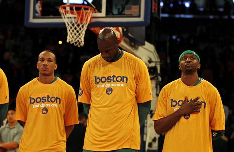 "Boston Celtics center Kevin Garnett (C) stands with his teammates during the national anthem wearing ""Boston stand as one"" t-shirts before t"
