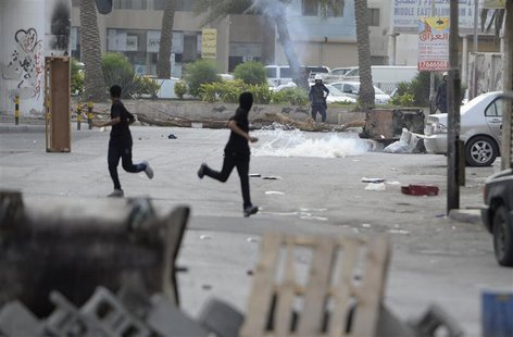 Protesters run for cover from the tear-gas fired by riot-police during clashes in the village of Jidhafs, west of Manama, April 20, 2013. RE