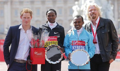 Britain's Prince Harry (L) and Virgin CEO Richard Branson (R) pose on the podium with London Marathon winners Tsegaye Kebede of Ethiopia (2n