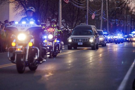 A hearse transporting the body of slain MIT police officer Sean Collier drives down Church Street near the Town Common in Wilmington, Massac