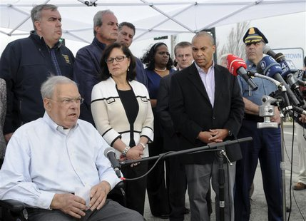Boston Mayor Tom Menino speaks from his wheelchair during a news conference, as Massachusetts Governor Deval Patrick and public safety offic