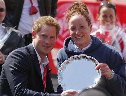 Britain's Prince Harry poses with Tatyana McFadden (R) of the U.S., winner of the women's wheelchair class of the London Marathon, during th